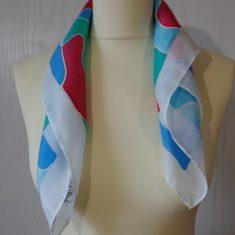 """Pañuelo de seda natural 55x55 cm ( 21,5""""x21,5"""") con motivo de ondas en diferentes tonos de azules y rojo."""